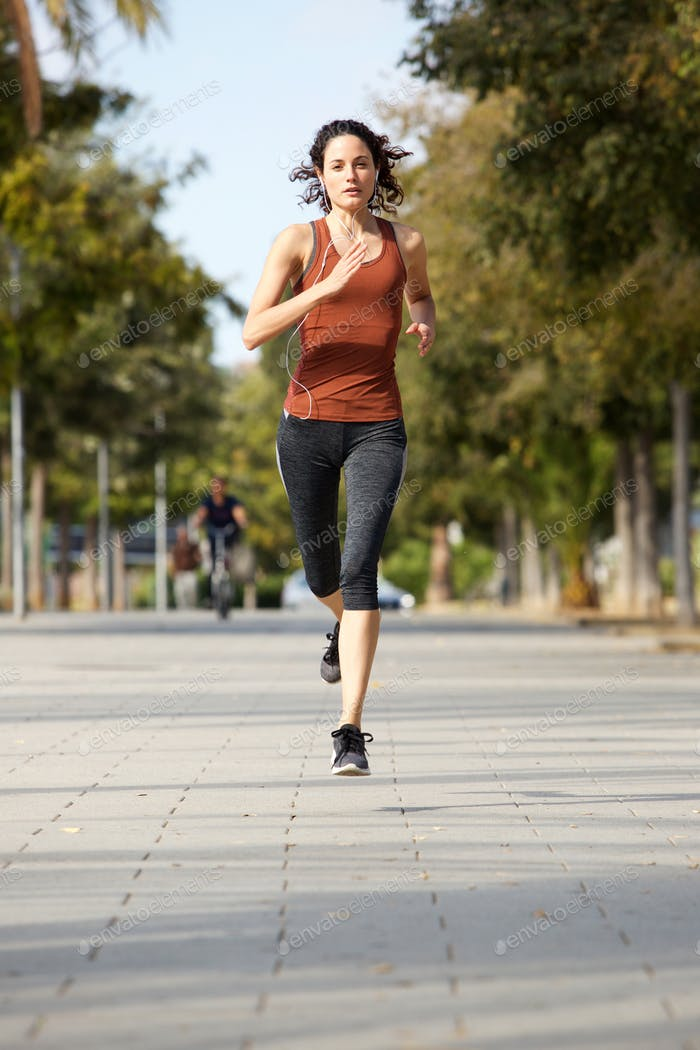 Full body healthy young sports woman jogging outdoors
