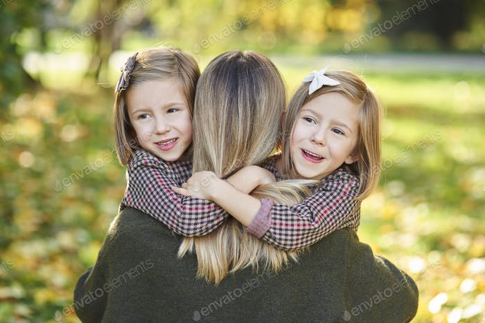 Two little girls embracing their mom