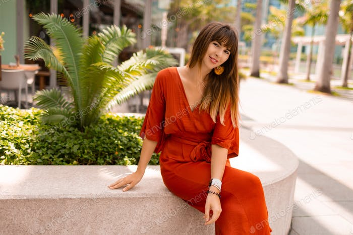 Confident traveling woman in orange dress sitting and looking  forward.