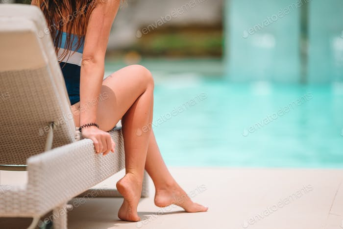 Woman sunbathing on a lounger at tropical resort