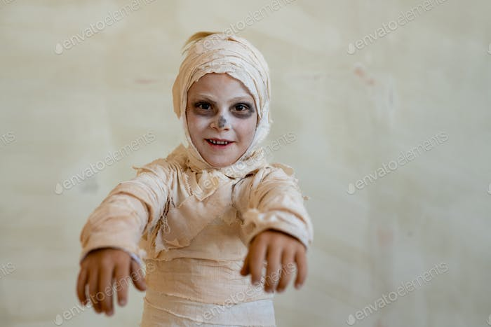 Boy in mummy costume acting like zombie