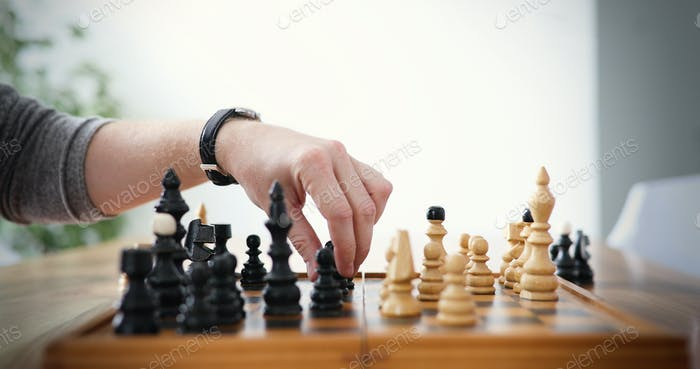 Close up of hands of man playing chess