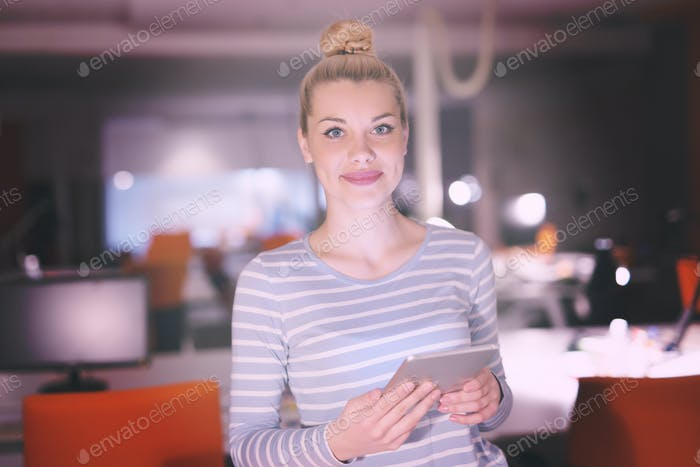 woman working on digital tablet in night office