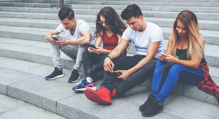 Gruppe von Freunden, die zusammen mit ihren Handys sitzen