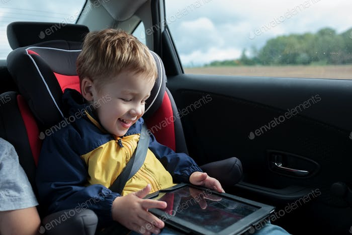 Happy boy playing with touchpad in the car