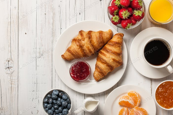 Breakfast with croissants, coffee, jam and berries