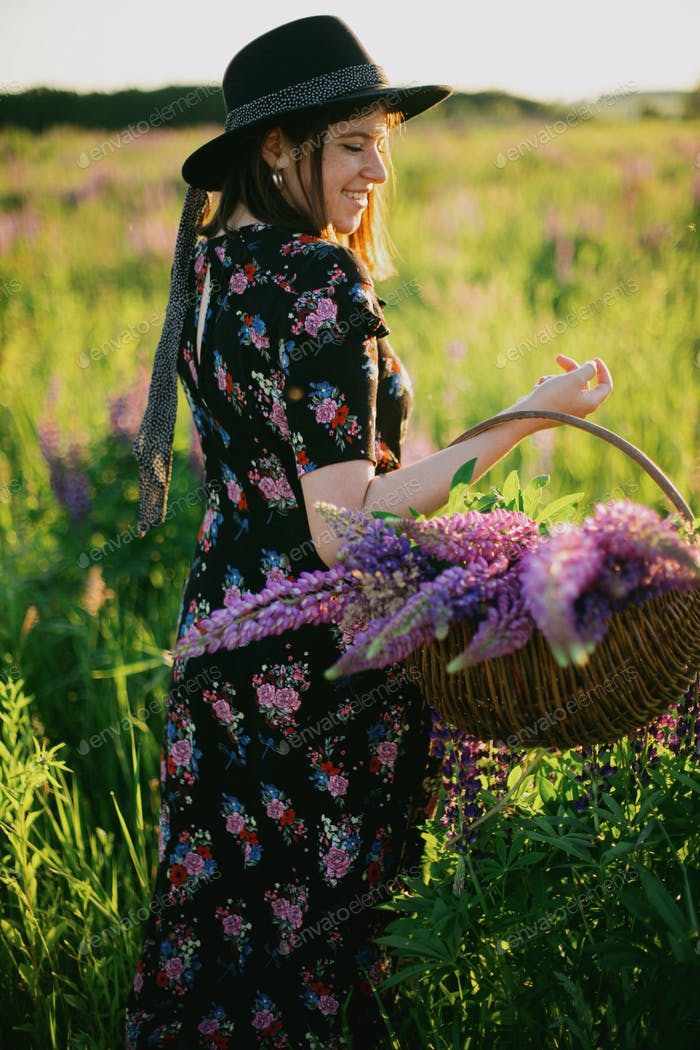 Beautiful woman walking in sunny lupine field with rustic basket and flowers. Tranquil moment