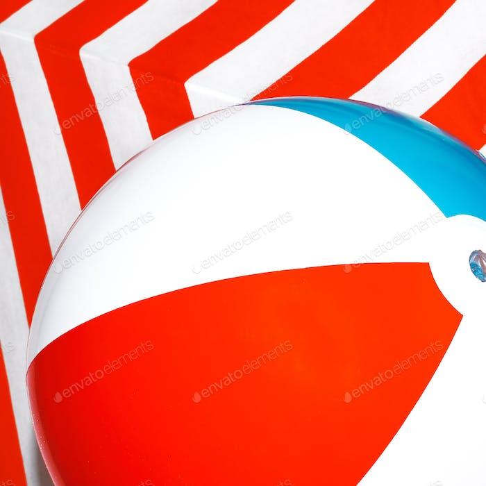 Strandball auf gestreiftem Hintergrund. Minimalistisch