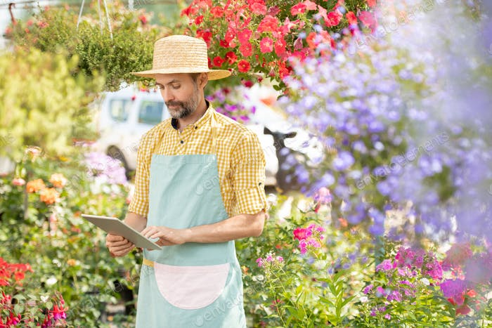 Mature gardener using remote search in tablet while looking for online data