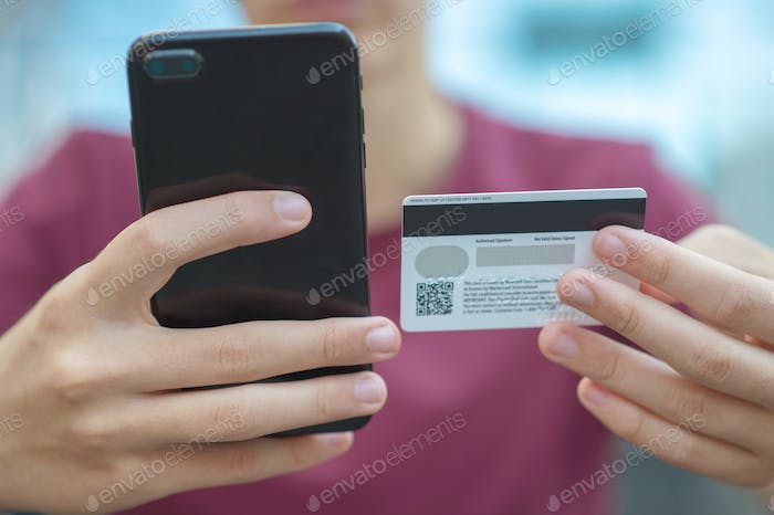 Close-up human hands with mobile phone and credit card.
