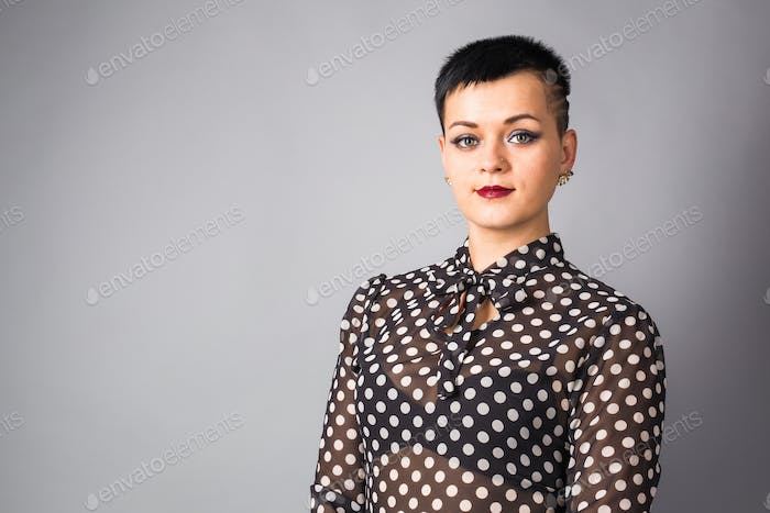 Portrait of business woman or creative professional. Grey background, with copy space.