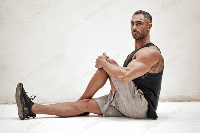 Portrait of a sportsman, stretching out his leg muscles in a sitting position
