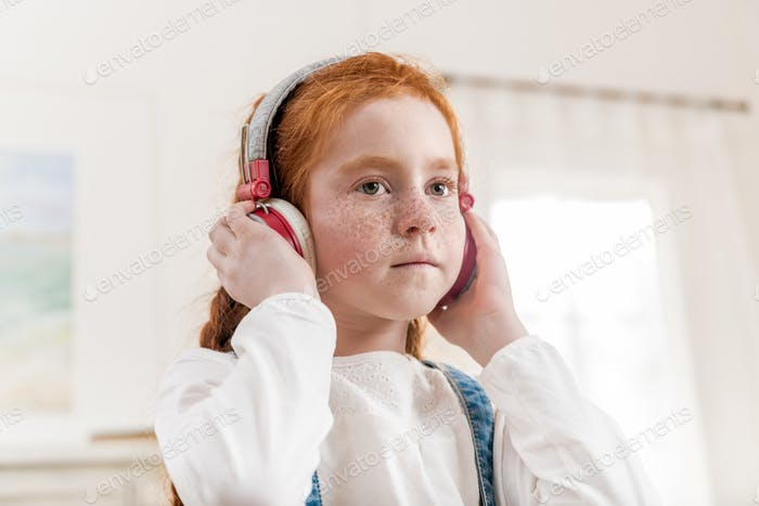 portrait of little girl listening music in headphones at home