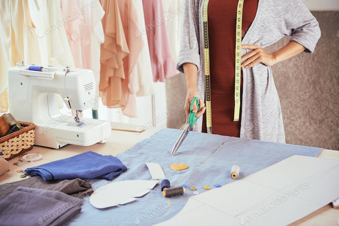 Crop tailor with scissors near table