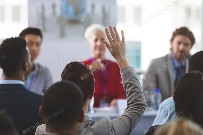 Businesswoman raising hand while woman allowed her to speak at business seminar in office building