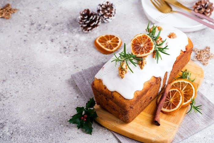 Obstbratentorte bestäubt mit Zuckerguss, Nüssen und trockenen Orange auf Steinhintergrund. Weihnachten und Winter