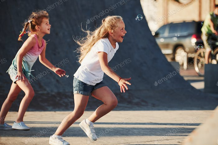 Having fun with bubbles. Leisure activities. Two little girls having fun in the park