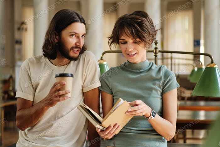 Young attractive casual students happily talking with coffee and book in library of university