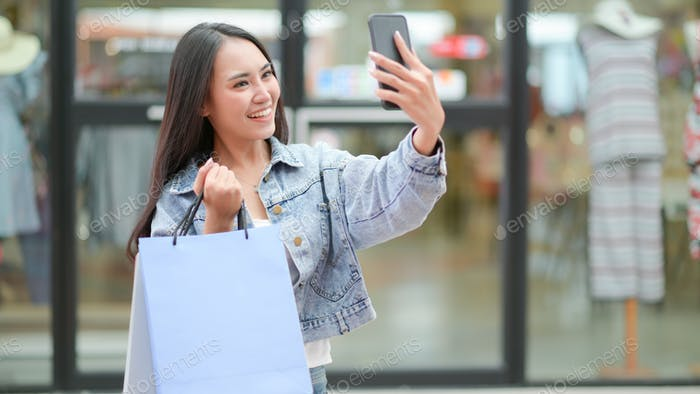 Asian shopper is using a smartphone to take a selfie. She stood and held a shopping bag.