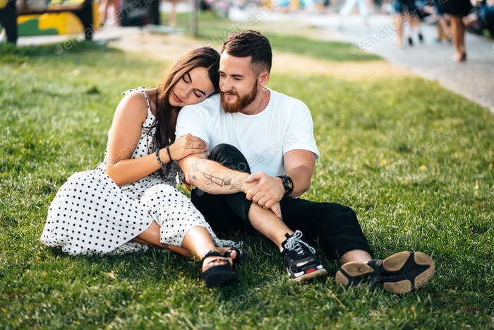 Beautiful young girl hugging her handsome guy in the park