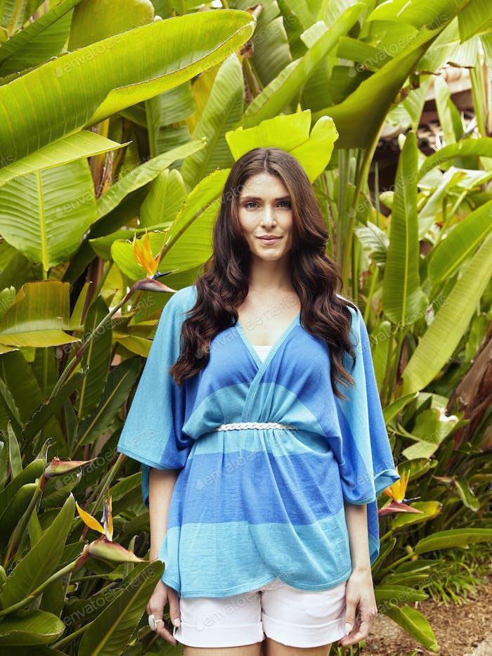 Caucasian woman standing in foliage
