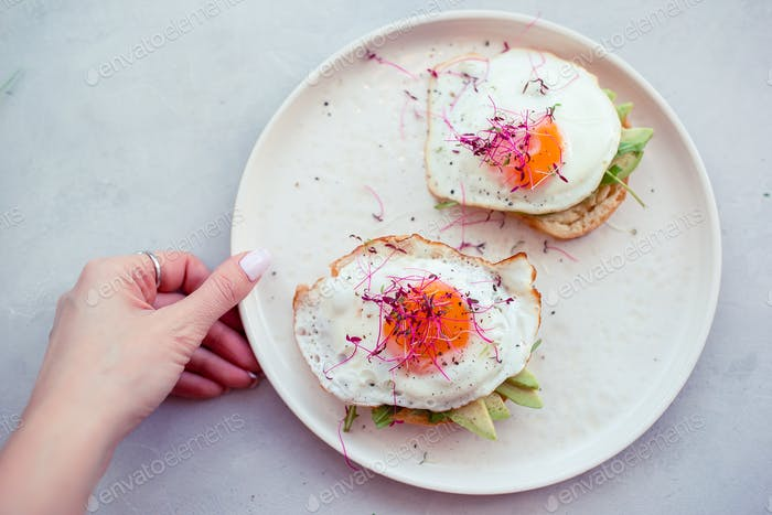 Healthy food concept. Tasty sandwich with avocado and fried eggs