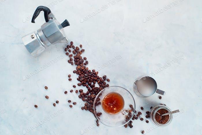 Gießen Kaffeebohnen aus Mokkakanne in einer Glas-Espressotasse mit einer Untertasse. Kreative Draufsicht heiß