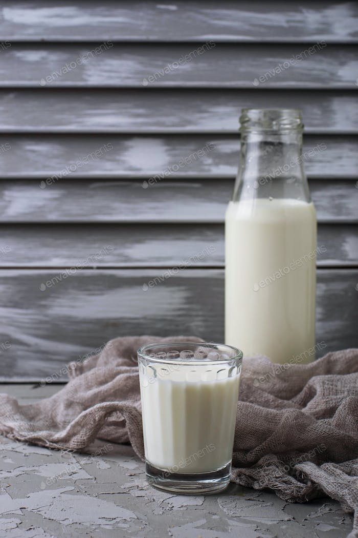 Glass and bottle of milk on gray concrete background