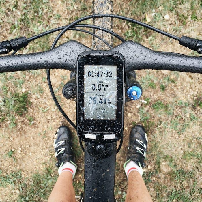 Bike computer navigator on black carbon bicycle in the rain. Waterproof display and activity data