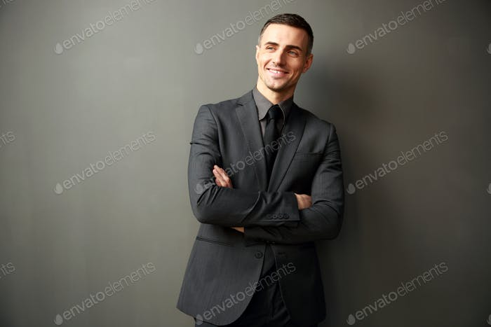 Cheerful businessman with arms folded standing on gray background