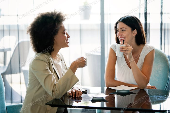 Communication and friendship concept. Smiling diverse women with coffee cups at cafe