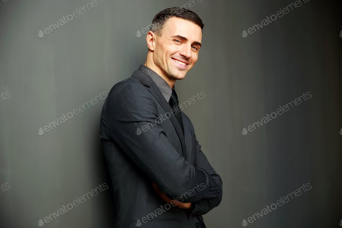 Smiling businessman with arms folded standing on gray background