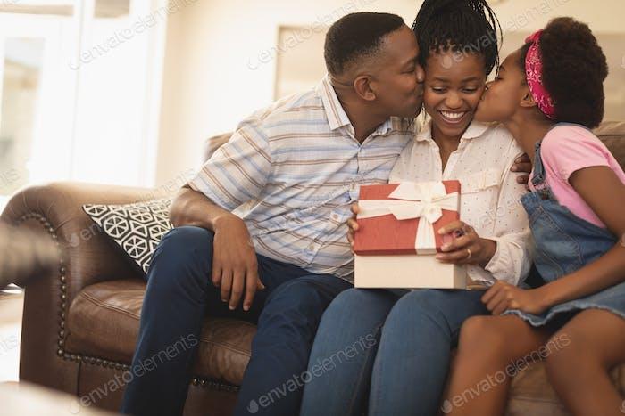 Porträt von glücklichen Afroamerikaner Vater und Tochter küssen Mutter auf Wangen zu Hause