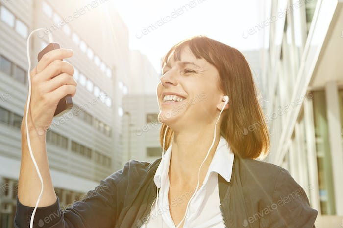 Happy woman holding cellphone with earphones in sunlight