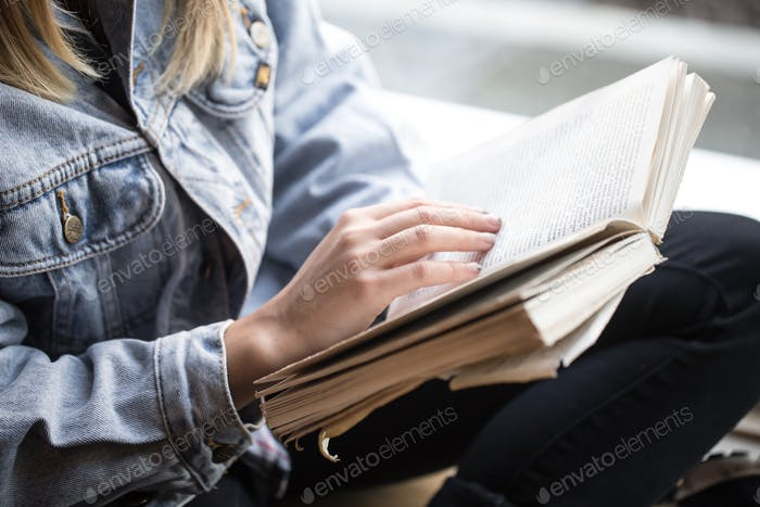 Young girl sitting in a cafe and reading a book