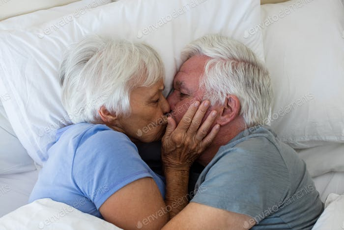 Senior couple kissing each other in bedroom