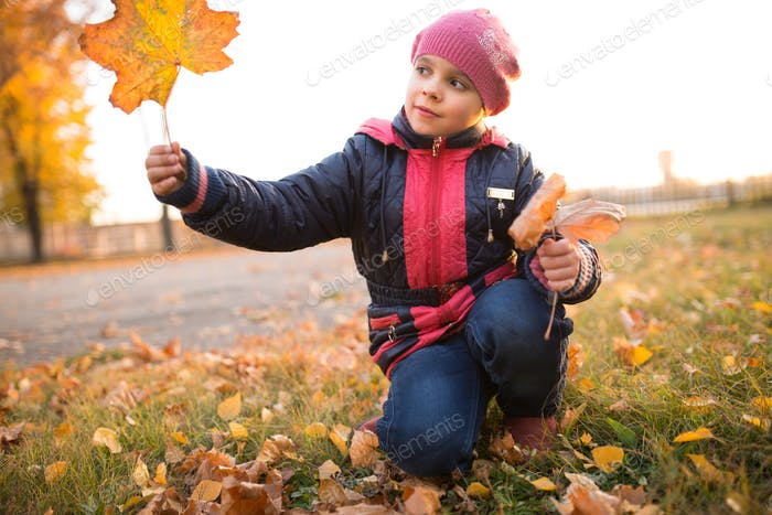 Little cheerful positive girl with a leaf