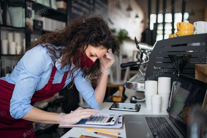 Frustrated coffee shop manager calculating figures in cafe, small business and new normal concept