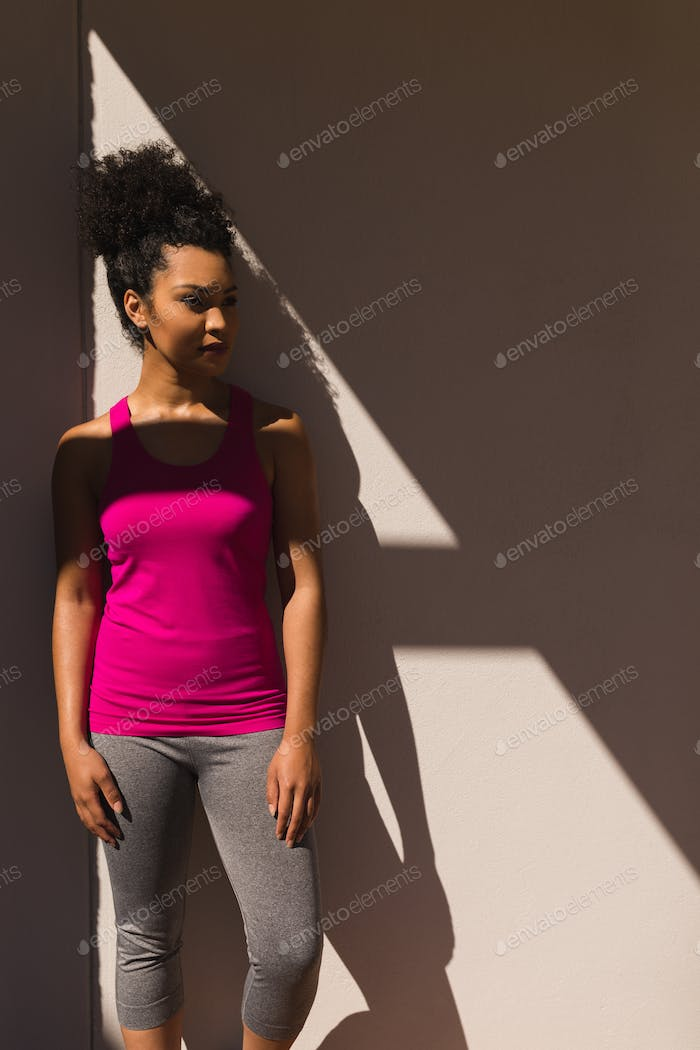 Front view of active young African American woman posing against wall in the backyard of home
