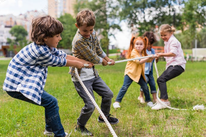 adorable happy kids playing tug of war in park