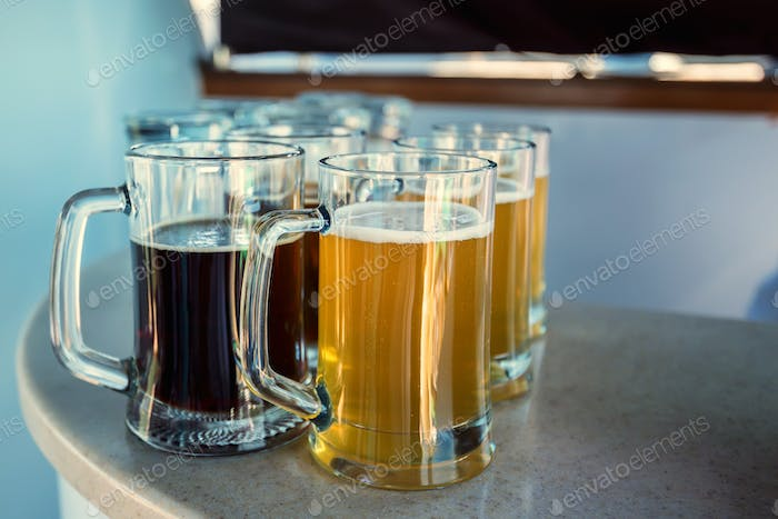 Glasses of dark and light beer placed on table