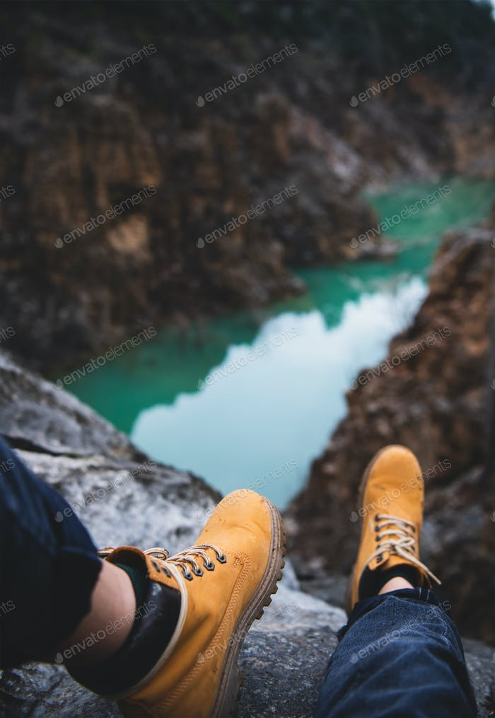 Feet of nature explorer sitting over mountain river canyon