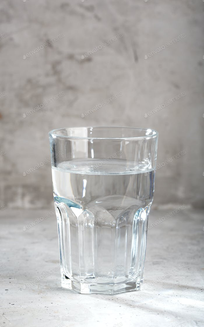A glass of clean water on a concrete background.