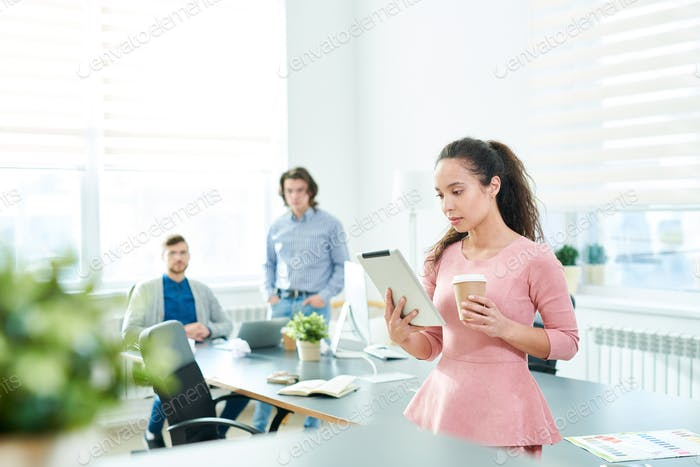 Hispanic female manager reading business article on tablet