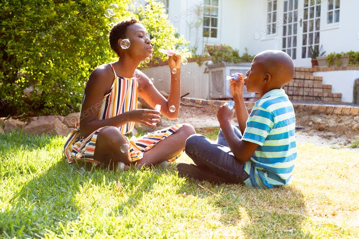African American woman and her son, spending time together in the garden