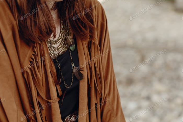 Gypsy girl in fringe jacket with feather bronze accessory