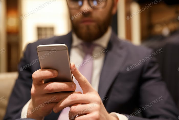 Concentrated young bearded businessman chatting by phone.