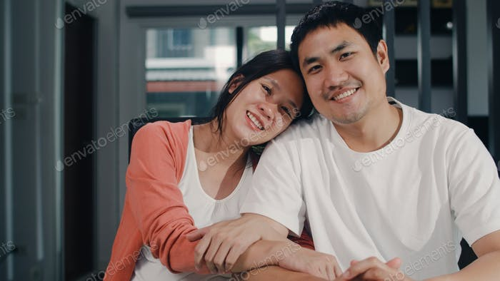 Portrait young Asian Pregnant couple relax toothy smile looking to camera at home.