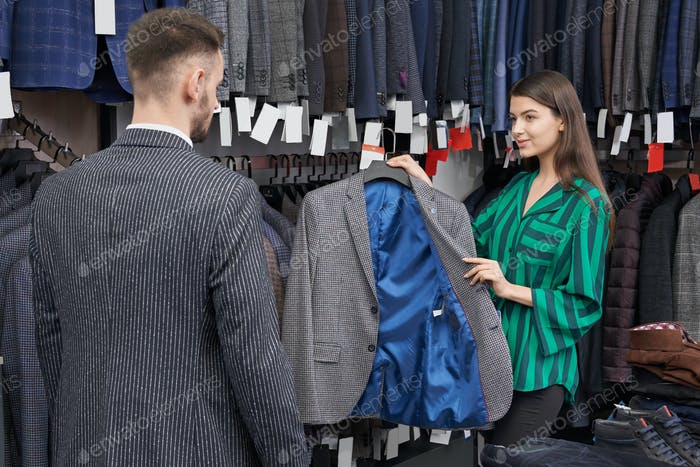 Shop consultant choosing and showing jacket for client