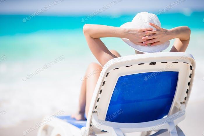 Junge Frau mit Hut auf einer Liege am tropischen Strand